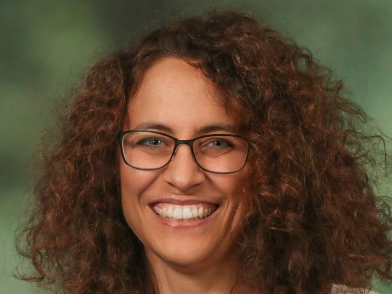 Rosaria Silipo, data science evangelist at Knime, is smiling into the camera while wearing glasses against a green background.